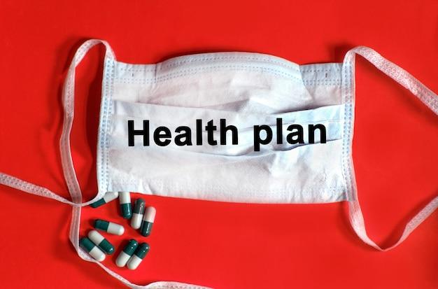 Gesundheitsplan - text auf einer schützenden gesichtsmaske, tabletten auf einem roten hintergrund