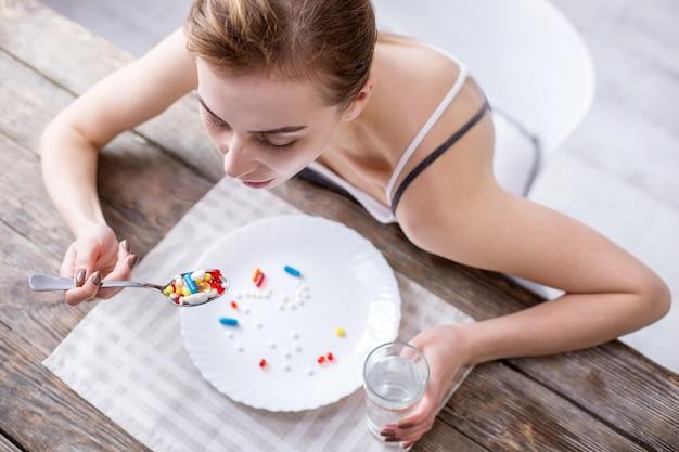 Gesundheitsprobleme. draufsicht einer traurigen jungen frau, die am tisch sitzt, während medizin hat