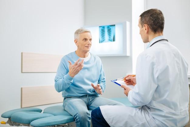 Gesundheitsprobleme. netter angenehmer älterer mann, der auf dem bett sitzt und gestikuliert, während er dem arzt über sein problem erzählt