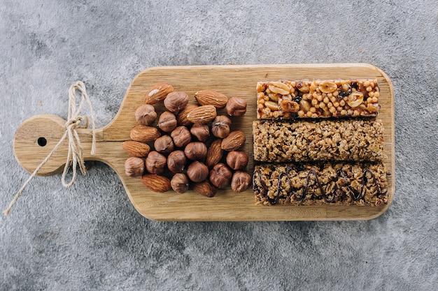 Gesundheitsriegel und gemischte nüsse. energieriegel mit mandeln und haselnüssen. snack für ein gesundes stillleben