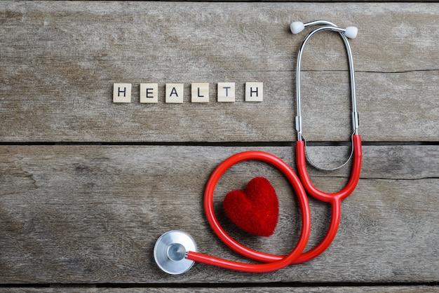 Gesundheitstextwort gemacht mit hölzernen blöcken und rotem herzen, stethoskop auf holztisch