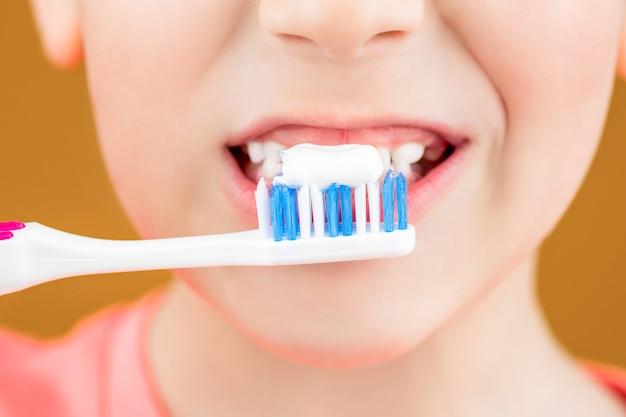 Gesundheitsversorgung, zahnhygiene. frohes kind zeigt zahnbürsten. zähneputzen des kleinen jungen. zahnhygiene. glückliches kleines kind, das sich die zähne putzt. kinderjunge, der die zähne putzt. junge zahnbürste weiße zahnpasta.