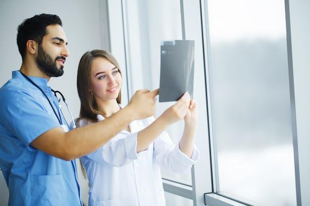 Gesundheitsvorsorge. ärzteteam, das röntgenbericht im korridor überprüft. medizinisches konzept