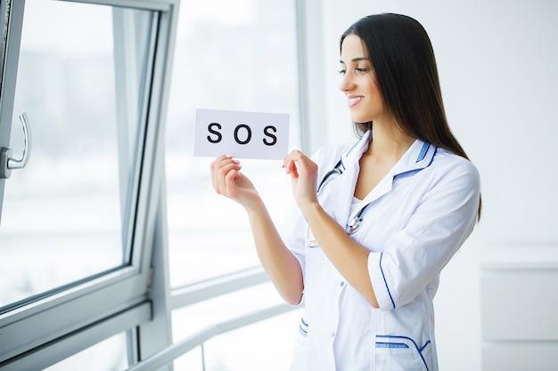 Gesundheitsvorsorge. doktor holding eine karte mit symbol-hilfe, medizinisches konzept