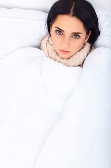 Gesundheitsvorsorge. nahaufnahme der schönen kranken frau mit den kopfschmerzen, den halsschmerzen und fieber bedeckt in der decke, die krank sich fühlt und misst körpertemperatur mit thermometer. krankheit und krankheit. hohe auflösung