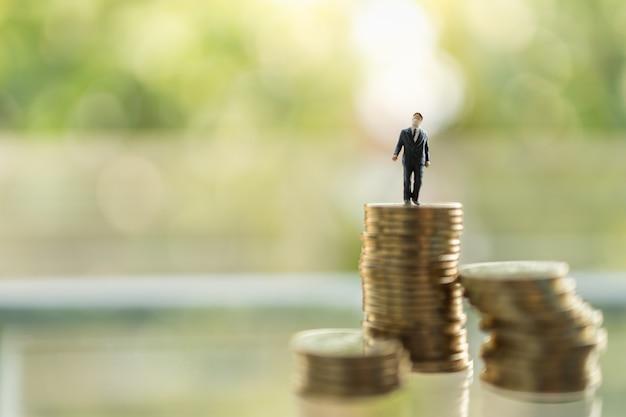 Gesundheitswesen, coronavirus (covid-19) situation business and econony cocept. geschäftsmann-miniaturfigurmenschen mit gesichtsmaske, die auf stapel von münzen mit kopienraum stehen.