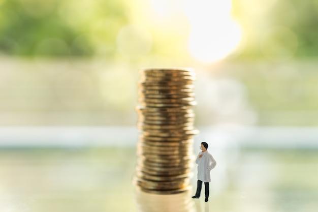 Gesundheitswesen, coronavirus (covid-19) situation geschäfts- und wirtschaftskonzept. doktor miniaturfigur menschen mit gesichtsmaske stehend mit instabilem stapel von münzen mit grüner natur