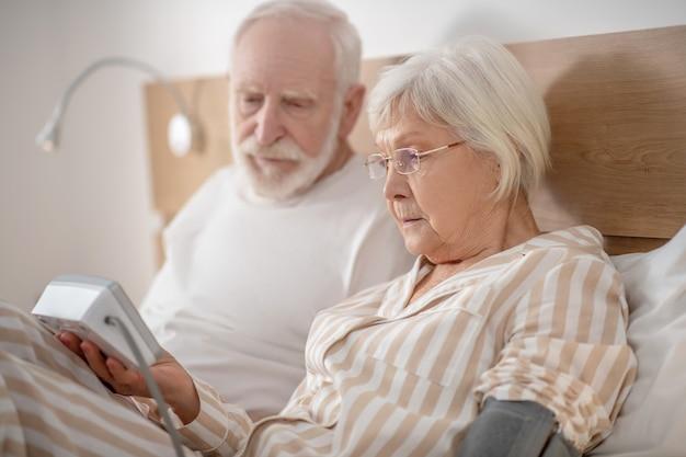 Gesundheitswesen. grauhaariger älterer mann, der im bett liegt und mit seiner frau den blutdruck überprüft