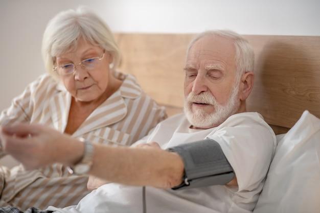 Gesundheitswesen. grauhaariger älterer mann, der seinen blutdruck überprüft und konzentriert aussieht