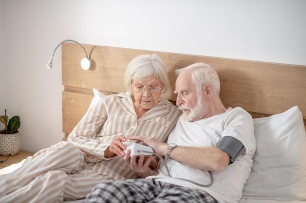 Gesundheitswesen. grauhaariger älterer mann, der zusammen mit seiner frau seinen blutdruck überprüft