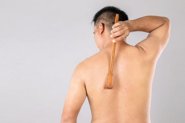 Gesundheitswesen oder juckreiz oder tinea cruris konzept: porträt von menschen mit scratch holz kleben an scratching auf seiner rückseite.