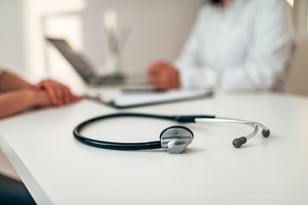 Gesundheitswesen und medizin-konzept. medizinisches stethoskop auf dem schreibtisch. arzt und patient im hintergrund.