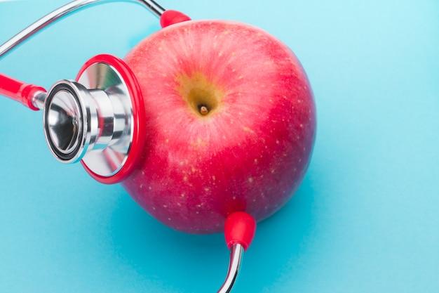 Gesundheitswesen und medizin stethoskop und roter apfel gesund und versicherungskonzept