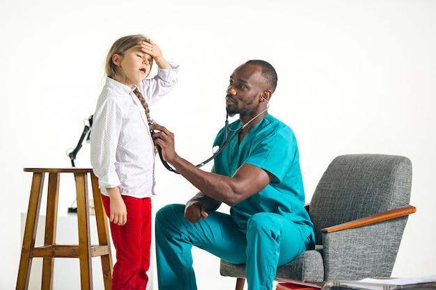 Gesundheitswesen und medizinisches konzept - arzt mit stethoskop, der auf die brust des kindes im krankenhaus hört