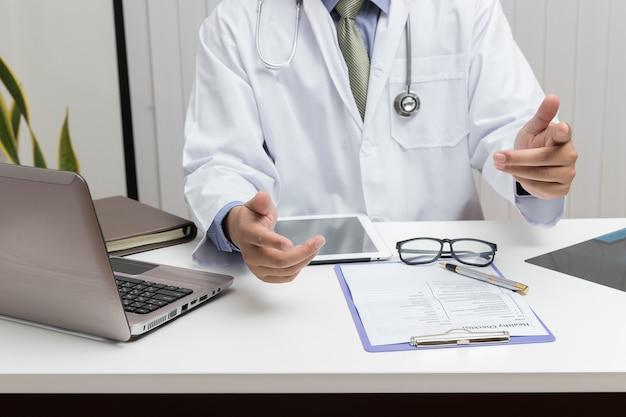 Gesundheitswesen und medizinisches konzept, doktor, der tablette verwendet und im büro arbeitet.
