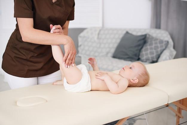 Gesundheitswesen und medizinisches konzept. eine professionelle masseurin macht einem kleinen baby eine massage und gymnastik in einem modernen, gemütlichen raum.