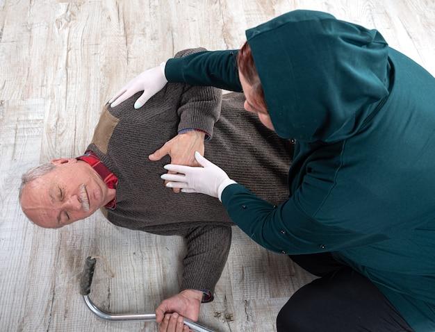 Gesundheitswesen und medizinisches konzept. frau, die einem älteren mann erste hilfe gibt