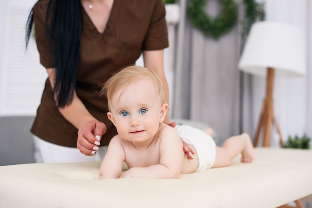 Gesundheitswesen und medizinisches konzept. glückliches baby, das massage mit professioneller masseurin hat. freundlicher und freundlicher kinderarzt. kindermassage auf der couch in einem modernen gemütlichen raum.