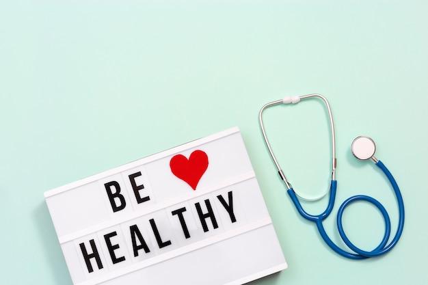 Gesundheitswesen und medizinisches konzept. leuchtkasten mit worten gesund sein und stethoskop gesundheitswünsche