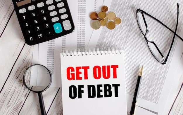 Get out of debt geschrieben in einem weißen notizblock in der nähe eines taschenrechners, bargeld, brille, lupe und stift