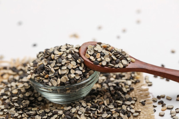 Geteilte schwarze linse auch bekannt als schwarzes gramm, schwarzer urad dal, vigna mungo, urad beani glasschale auf weißem hintergrund