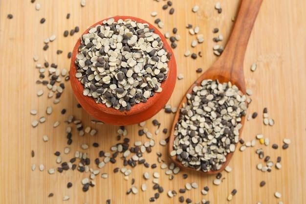 Geteilte schwarze linse auch bekannt als schwarzes gramm, schwarzer urad dal, vigna mungo, urad bohne auf hölzernem hintergrund.