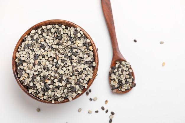 Geteilte schwarze linse auch bekannt als schwarzes gramm, schwarzer urad dal, vigna mungo, urad bohne in der holzschale auf weißem hintergrund