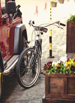 Getönt von vintage-fahrrad, das mit kette an auto gehängt ist