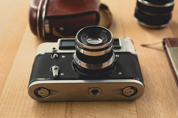 Getönte aufnahme einer manuellen retro-kamera mit porträtobjektiv, die auf einem holzschreibtisch liegt