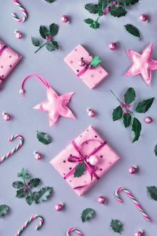 Getönten zweifarbigen duochromen weihnachtshintergrund mit rosa geschenkboxen, gestreiften zuckerstangen, schmuckstücken und dekorativen sternen.