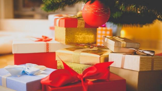 Getöntes bild eines großen haufens von weihnachtsgeschenken in kisten, die unter dem weihnachtsbaum im wohnzimmer mit kamin liegen