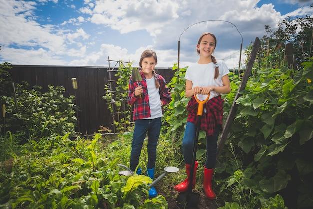 Getöntes bild von zwei jungen schwestern, die im hinterhofgarten arbeiten working
