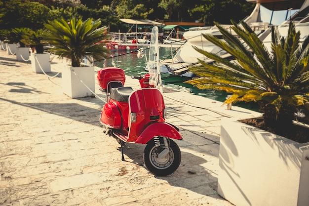 Getöntes foto von retro-rot-roller am seehafen geparkt