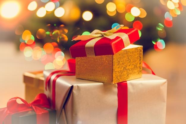 Getöntes foto von stapel geschenkboxen gegen weihnachtsbeleuchtung