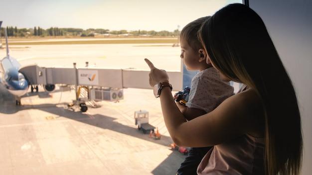 Getonte ansicht der jungen mutter, die ihrem kleinen sohn flugzeuge auf der landebahn am flughafen zeigt.