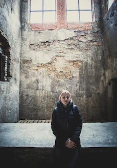 Getonte ansicht einer einsamen frau, die in einem verlassenen gebäude posiert