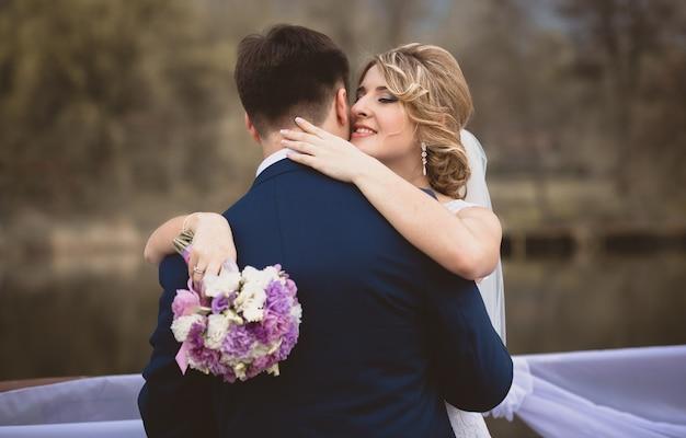Getonte aufnahme einer eleganten braut, die den bräutigam umarmt und an seinem ohr flüstert