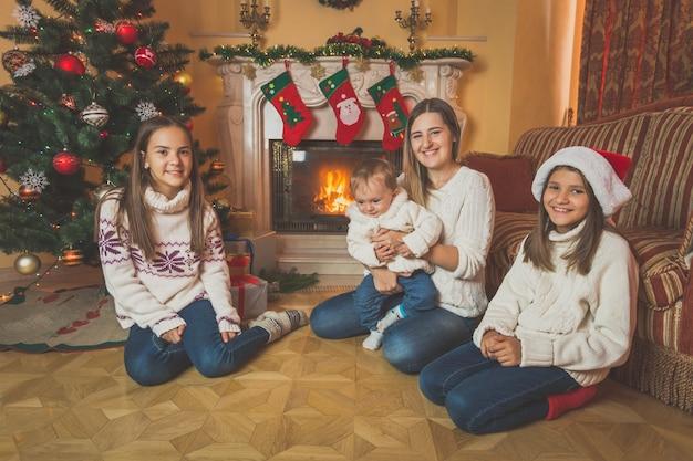 Getontes bild der glücklichen jungen mutter, die mit kindern auf dem boden am kamin sitzt. geschmückter weihnachtsbaum im hintergrund.