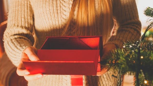 Getontes bild der jungen frau mit offenem rotem kasten mit weihnachtsgeschenk