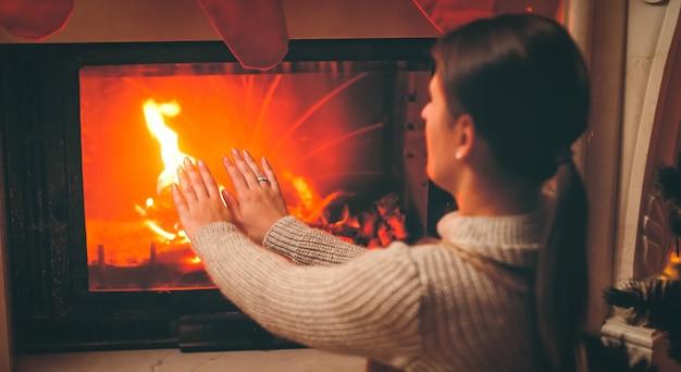 Getontes bild einer schönen frau, die sich kalt fühlt, wenn sie am brennenden kamin im wohnzimmer sitzt?