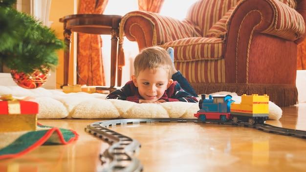 Getontes bild eines lächelnden kleinen jungen, der mit seiner neuen spielzeugeisenbahn und eisenbahn auf holzboden spielt. kind, das an neujahr oder weihnachten geschenke und spielzeug erhält