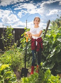 Getontes bild eines schönen teenager-mädchens, das auf der farm im garten arbeitet?