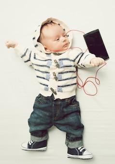 Getontes foto von süßem baby, das musik mit kopfhörern hört