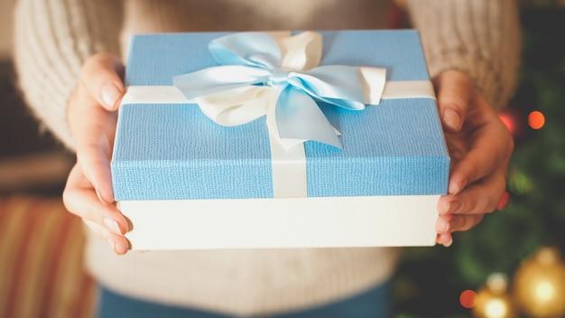 Getontes nahaufnahmebild der jungen frau weihnachtsgeschenkbox, die es in der kamera zeigt. perfektes bild für winterferien und feiern