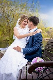 Getontes porträt der glücklichen braut, die auf den händen des bräutigams auf der bank im park sitzt