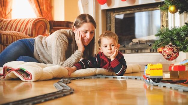 Getontes porträt der lächelnden familie, die den weihnachtsmorgen genießt und mit der spielzeugeisenbahn spielt. kind, das an neujahr oder weihnachten geschenke und spielzeug erhält