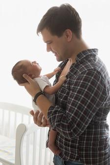 Getontes porträt des glücklichen vaters, der neugeborenes baby hält