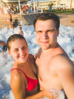 Getontes porträt eines glücklichen jungen paares, das ein selfie-porträt der seifenschaum-disco-party am meeresstrand macht