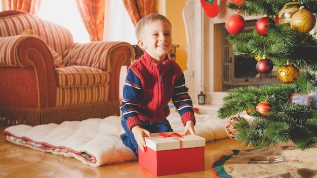 Getontes porträt eines lachenden kleinen jungen, der morgens zu weihnachten seine geschenke und geschenke erhält