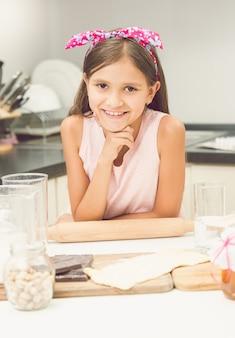 Getontes porträt eines süßen lächelnden mädchens, das während der teigherstellung in der küche posiert